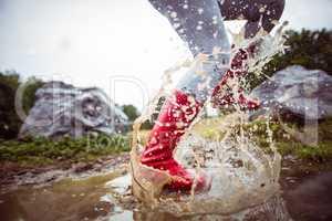 Woman splashing in muddy puddles