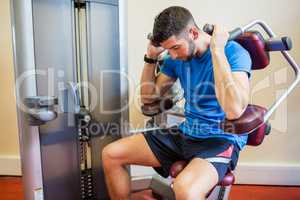 Concentrating man using weights machine