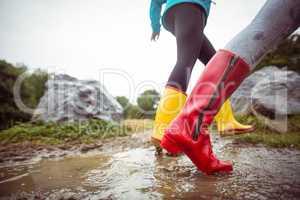 Women splashing in muddy puddles