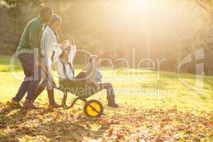 Young parents holding their children in a wheelbarrow