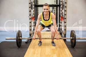 Concentrated woman about to lift a barbell and weights