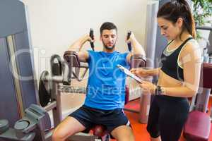 Concentrating man using weights machine with trainer