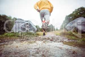 Man jogging through muddy puddles