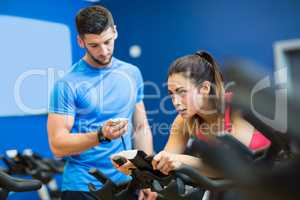 Woman on exercise bike with trainer timing her