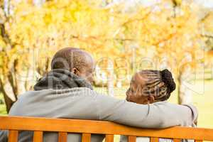 Happy senior couple discussing together on a bench