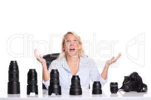 Frau sitzt vor verschiedenen Objektiven und kann sich nicht entscheiden