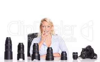 Fotografin sitzt vor verschiedenen Objektiven und überlegt