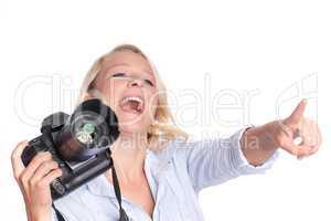 Lachende Fotografin zeigt mit dem Finger auf etwas