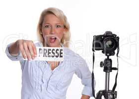 Energische Pressefotografin mit Kamera hält ein Presseschild