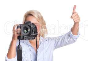 Fotografin schaut durch eine Kamera und zeigt Daumen hoch
