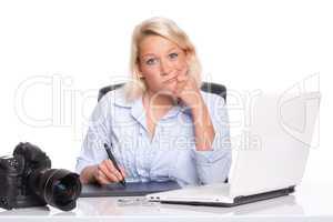 Grafikerin sitzt an einem Zeichentablett und zieht eine Schnute
