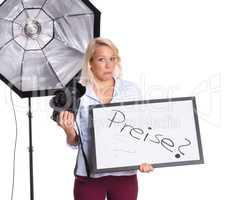 Fotografin mit Kamera hält eine Preistafel und ist skeptisch