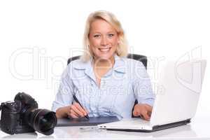 Fotografin bearbeitet Fotos am Laptop und lächelt