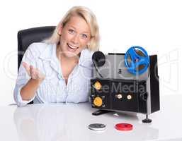 Blonde Frau präsentiert einen alten Filmprojektor