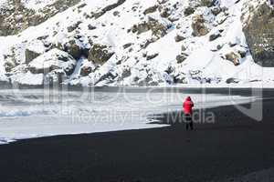 Woman walks along black sand beach in Vik, Iceland