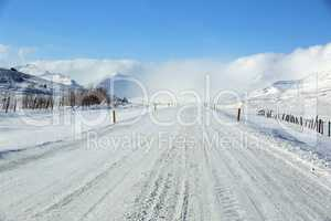 Snowy and icy road with volcanic mountains in wintertime