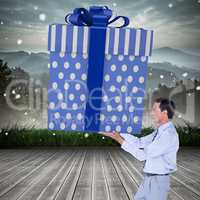 Composite image of stylish man with giant gift