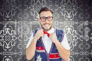 Composite image of geeky hipster wearing christmas vest