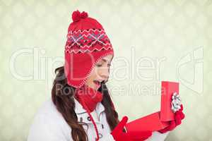 Composite image of happy brown hair opening christmas gift