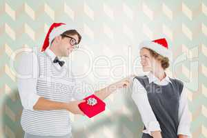 Composite image of geeky hipster offering present to his girlfri