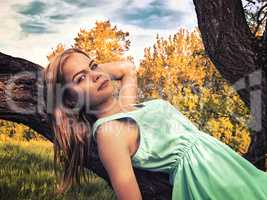 Young sensual blonde girl lying on a tree branch
