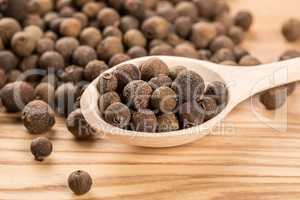allspice in a wooden spoon on the wood table
