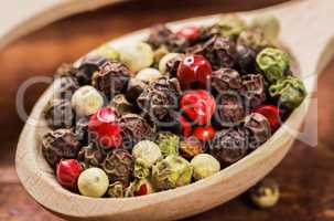 Pepper seeds in wooden spoon on wood table