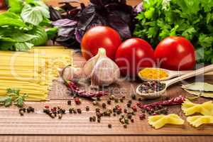 Raw pasta, vegetables, basil and spices on the wood table