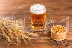 Oktoberfest Beer Mug and traditional German pretzels with wheat cones on the wood  table