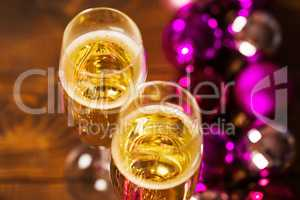 Two Glasses With Champagne and Christmas Tree Decorations on the table.