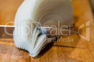 Macro of knife cutting through white onion layers