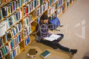 Student reading book in library on floor