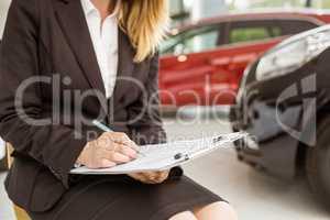 Saleswoman sitting near cars while writing on clipboard