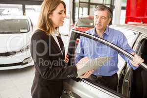 Smiling businessman undersign a car contract