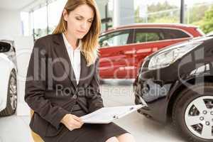 Smiling saleswoman sitting near cars