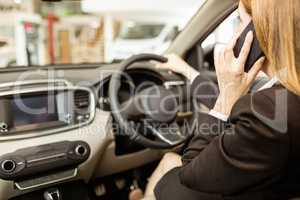 Businesswoman having a phone call while siting in a car