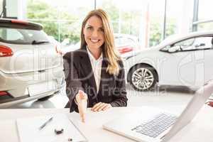 Smiling saleswoman ready to shake hand