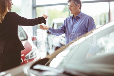 Saleswoman giving car keys while shaking hand of a client