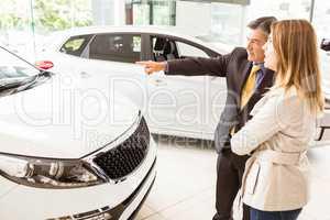 Salesman showing a car to a client