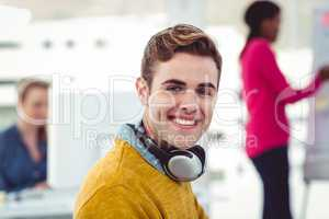 Graphic designer wearing headphones at desk