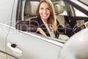 Smiling businesswoman siting in a car