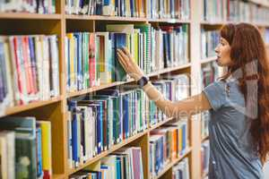 Mature student picking book in library wearing smart watch