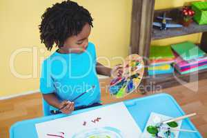 Child using paints to make a picture