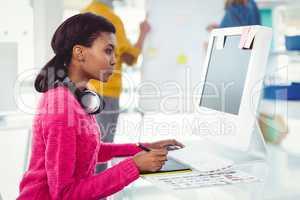 Creative businesswoman wearing headphones at her desk