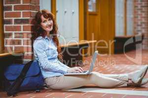 Mature student using laptop in hallway