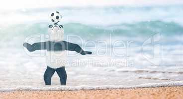 miniature circus bamboo panda teddy bear stands on beach Gulf of Siam to his ankles in water. and chasing ball on nose. soccer player juggling beautiful background blur on the beach