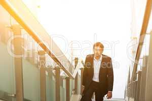 Indian businessman ascending steps.