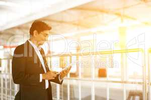 Businessman using tablet computer at railway station