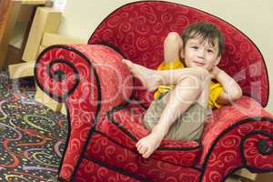 Mixed Race Boy Relaxing in Comfortable Red Arm-Chair