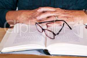 Hands of an elderly woman lying on the book